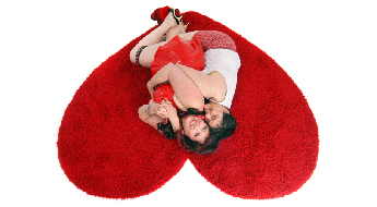 Performance artists and activists Annie Sprinkle and Elizabeth Stephens hug on a rug in the shape of a heart.