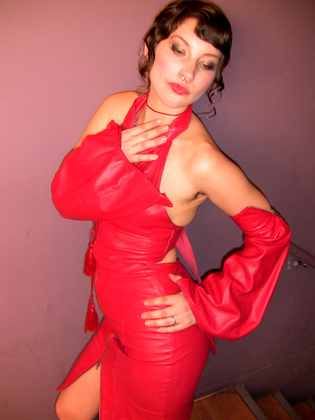 A sultry model wears a gorgeous red dress by Miss Velvet Cream.